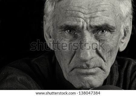 portrait of an elderly man on black background - stock photo
