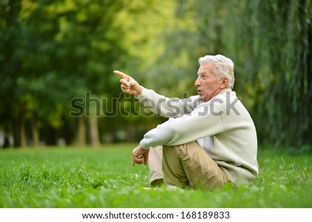 Portrait of an elderly man sitting on grass and pointing