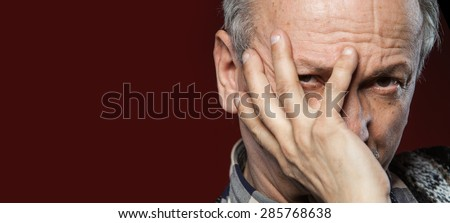 Portrait of an elderly man with face closed by hand on red background and copy-space - stock photo