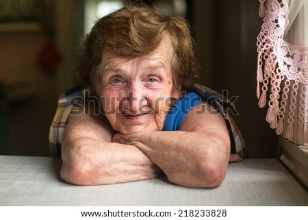 Portrait of an elderly smiling woman, close-up inside house. - stock photo