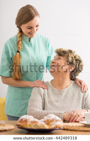 Portrait of an elderly woman and her home nurse standing behind her in an affectionate pose