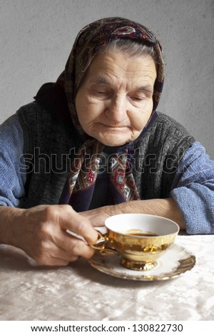 Portrait of an elderly woman drinking coffee on a vintage background. Dreaming the past - stock photo