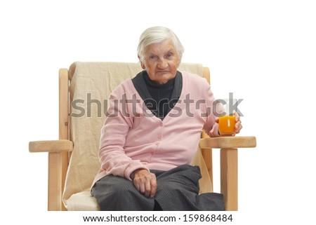 Portrait of an elderly woman drinking orange juce - stock photo