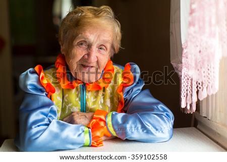 Portrait of an elderly woman in ethnic costume. - stock photo