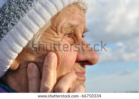 Portrait of an elderly woman, lost in thought, looks into the distance - stock photo