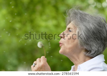 Portrait of an elderly woman on a walk in the park in late spring - stock photo