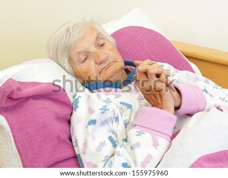 Portrait of an elderly woman praying in her bed - stock photo
