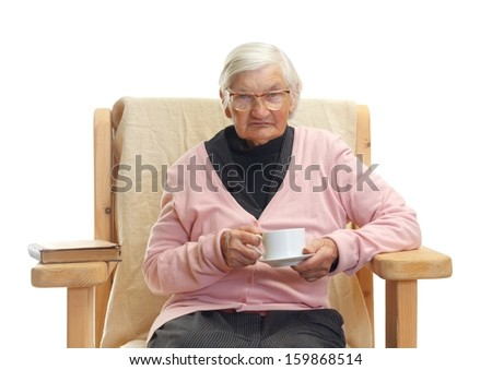 Portrait of an elderly woman reading a book and drinking coffe - stock photo