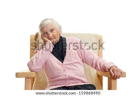 Portrait of an elderly woman sitting in a chair - stock photo