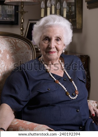 Portrait of an elderly woman sitting in an armchair, looking at the camera