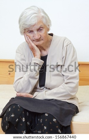 Portrait of an elderly woman sitting on the bed - stock photo