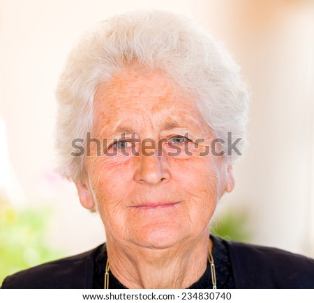 Portrait of an elderly woman smiling at the camera - stock photo