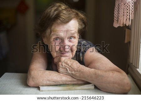 Portrait of an elderly woman with expressive look in her house.