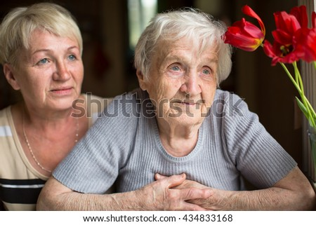 Portrait of an elderly woman with her adult daughter in the background. - stock photo