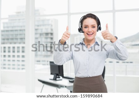 Portrait of an elegant businesswoman wearing headset while gesturing thumbs up in the office - stock photo