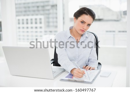 Portrait of an elegant businesswoman with graphs and laptop in bright office