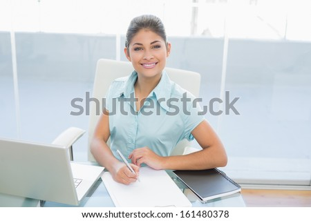 Portrait of an elegant businesswoman with laptop writing document at desk in a bright office
