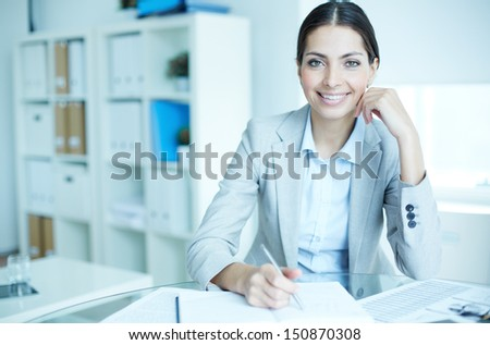 Portrait of an elegant manager sitting at her workplace - stock photo