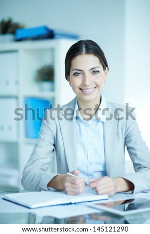 Portrait of an elegant manager sitting at her workplace and looking at camera