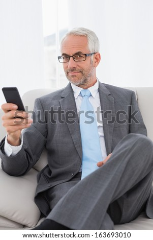 Portrait of an elegant mature businessman text messaging on sofa in living room at home