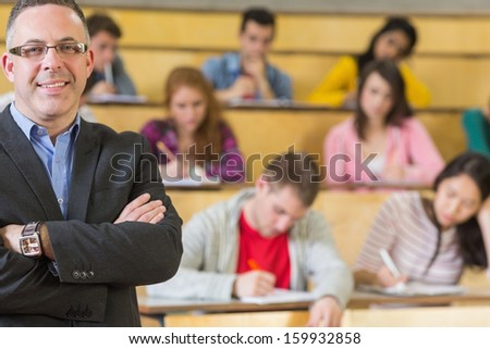 Portrait of an elegant teacher with students sitting at the college lecture hall