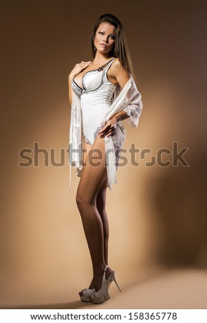 Portrait of an elegant woman who is posing and wearing lingerie and high heels over a dark background