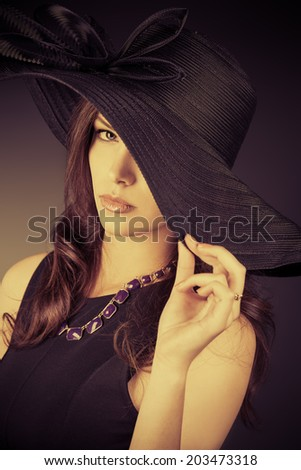 Portrait of an elegant young woman in a hat over dark background.