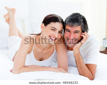 Portrait of an enamored couple embracing lying on their bed - stock photo