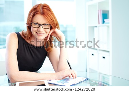 Portrait of an enthusiastic business lady analyzing financial report - stock photo
