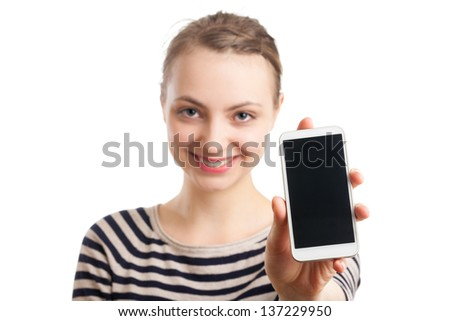 Portrait of an European blond woman in her twenties, showing her white, blank cell phone screen. Focus on the phone, face blurred in the back. Isolated on white background. - stock photo