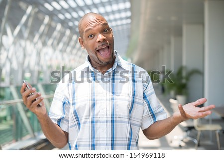 Portrait of an excited and funny black man because nobody'??s answering his telephone call - stock photo