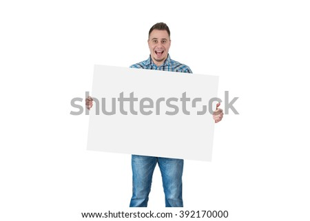 portrait of an excited attractive young man holding wide blank white card against white background