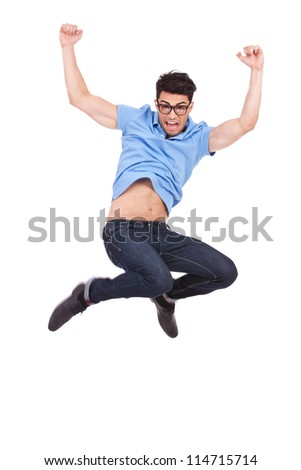 Portrait of an excited young casual man jumping in air and shouting, against white background