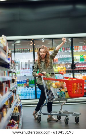 Portrait of an excited young casual woman doing grocery shopping with food cart at supermarket