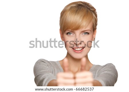 Portrait of an excited young woman gesturing a thumbs up sign against white background - stock photo