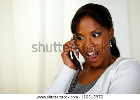 Portrait of an excited young woman screaming and talking on phone at soft colors composition - stock photo
