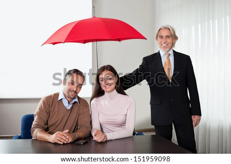 Portrait of an executive  holding an umbrella over a young couple. - stock photo