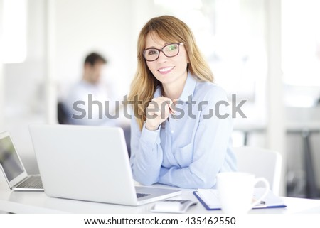 Portrait of an executive investment advisor professional woman sitting at office and working on laptop.