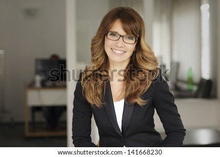 Portrait of an executive professional mature businesswoman sitting in office and smiling. Shallow focus. - stock photo