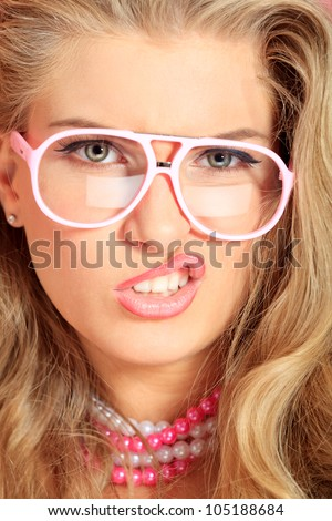 Portrait of an expressive blonde woman in pink spectacles posing in studio. - stock photo