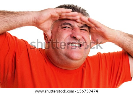 Portrait of an expressive man suffering from a severe headache against white background - stock photo