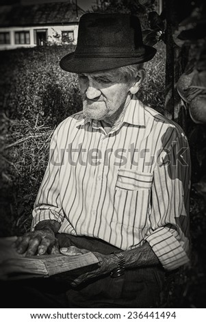 Portrait of an expressive old farmer reading leaning on an apple tree. Close-up portrait. Black and white picture. - stock photo