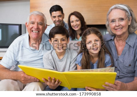 Portrait of an extended family looking at their album photo in the living room - stock photo