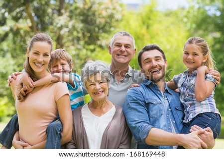Portrait of an extended family smiling at the park - stock photo