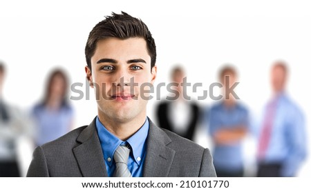 Portrait of an handsome businessman in front of his working team - stock photo