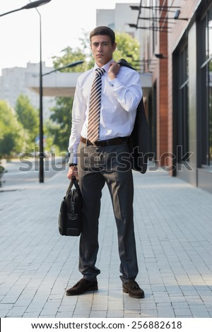 Portrait of an handsome businessman standing in an urban environment