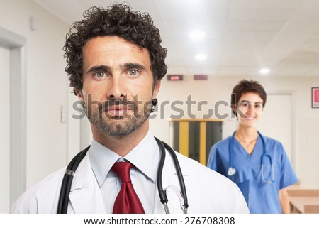 Portrait of an handsome doctor. Nurse in the background - stock photo