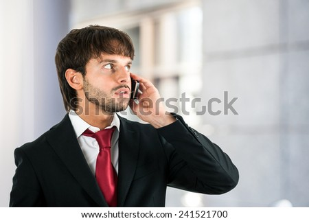 Portrait of an handsome executive talking on the phone - stock photo