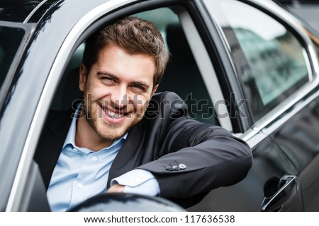 Portrait of an handsome guy driving his car - stock photo