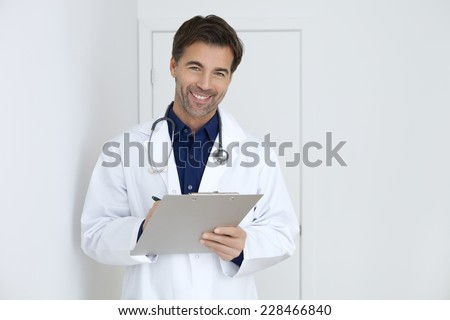 Portrait of an handsome male doctor visiting his patient and taking notes on a clipboard.This photo has been produced with professionals. - stock photo